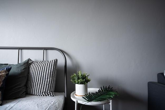 Canto do quarto com plantas artificiais em tinta de mármore branco cerâmica padrão na mesa lateral de metal branco em estilo escandinavo moderno