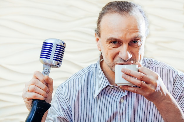 Cantor com microfone antigo bebe café
