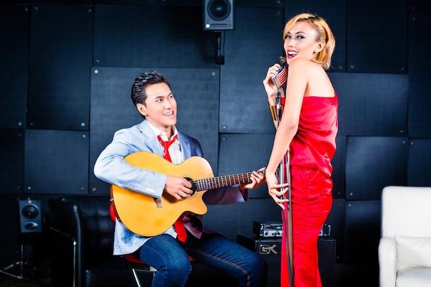 Cantor e guitarrista profissional asiático gravando uma nova música ou cd de álbum em estúdio