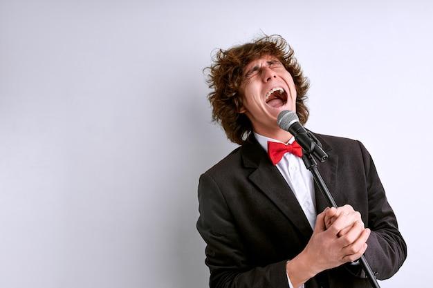 Cantor em performance cantando no microfone, artista expressivo se esforça ao máximo para agradar o espectador