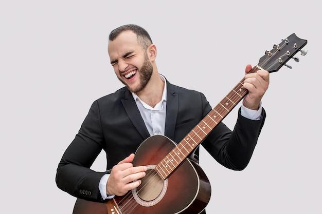 Cantor em terno preto ficar e tocar violão. ele canta música. jovem usa terno.