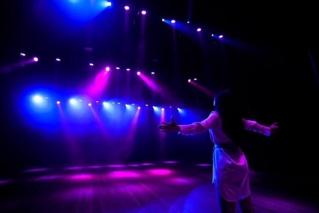 Cantor irreconhecível no palco diante do microfone, vista traseira, luzes de néon