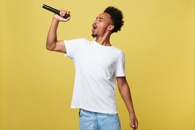 Cantor masculino americano africano, realizando com microfone.