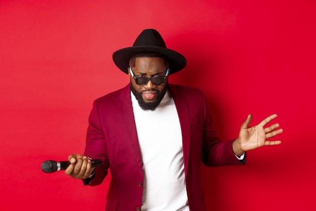Cantor negro apaixonado realizando contra um fundo vermelho, cantando no microfone, vestindo roupa de festa, em pé sobre um fundo vermelho.