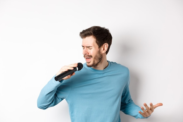 Cantor realizando música em fundo branco. jovem cantando no microfone no karaokê.