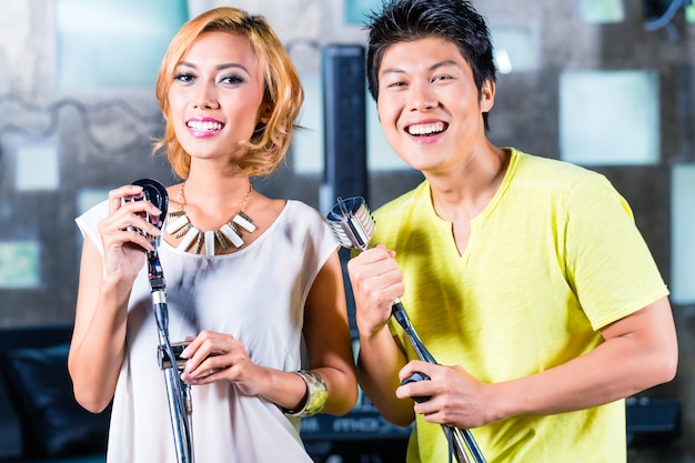 Cantora asiática produzindo música no estúdio de gravação