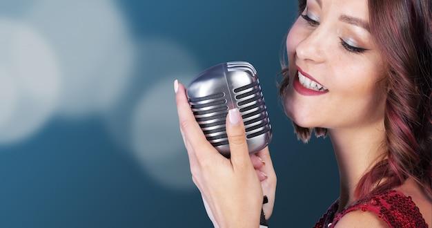 Cantora bonita e elegante com um microfone