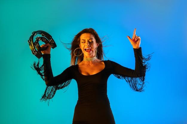 Cantora branca com pandeiro isolado no fundo azul do estúdio em luz de néon