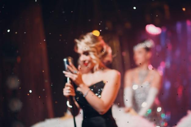 Cantora burred com microfone no palco e brilhos em primeiro plano