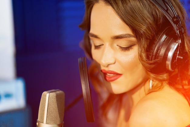 Cantora caucasiana com fones de ouvido e olhos fechados canta no microfone em um estúdio de gravação.
