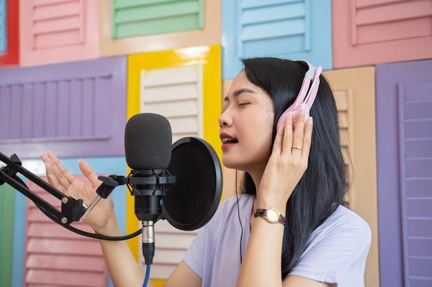 Cantora com fones de ouvido cantando com microfone contra o fundo colorido da parede de madeira