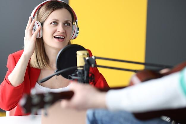 Cantora com fones de ouvido cantando música no microfone no conceito de trabalho de rádio de estúdio de gravação