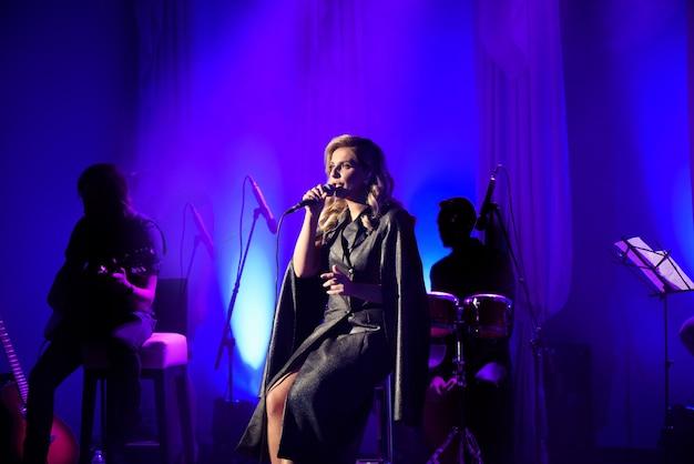 Cantora com microfone no palco na iluminação cênica.