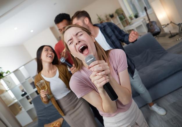 Cantora de karaokê linda jovem segurando o microfone e cantando enquanto joga karaokê com os melhores