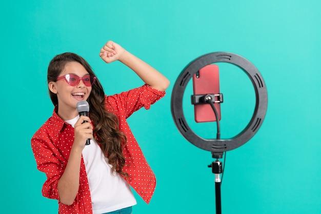 Cantora de menina adolescente feliz em óculos de sol cantando uma música no blog de vídeo musical de câmera blogando online com selfie led e microfone, karaokê online.