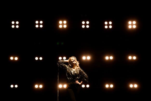 Cantora em cena no clube. iluminação de palco brilhante.