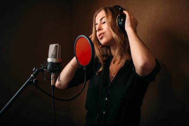 Cantora em fones de ouvido contra microfone