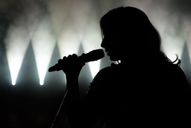 Cantora em silhueta. imagem aproximada do cantor ao vivo no palco