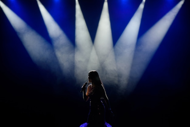 Cantora em silhueta. uma cantora jovem no palco durante um concerto.