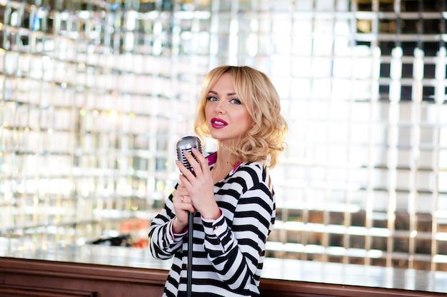 Cantora em um vestido longo perto do microfone.