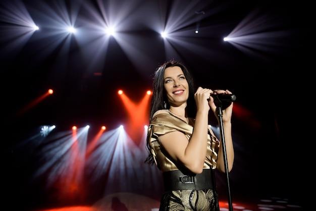 Cantora em um vestido no palco sob os raios de luz brilhante com fumaça.