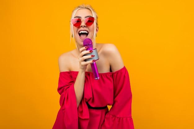Cantora em um vestido vermelho brilhante com ombros nus, com um microfone nas mãos na parede laranja