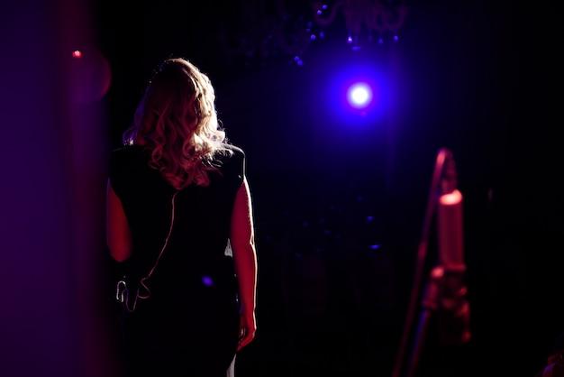 Cantora feminina, apresentando seu som vocal. com lente flare e holofote.