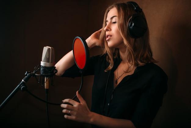 Cantora gravando uma música em estúdio musical