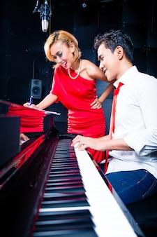 Cantora profissional asiática e pianista trabalhando e discutindo sobre uma nova música em estúdio para composição e gravação