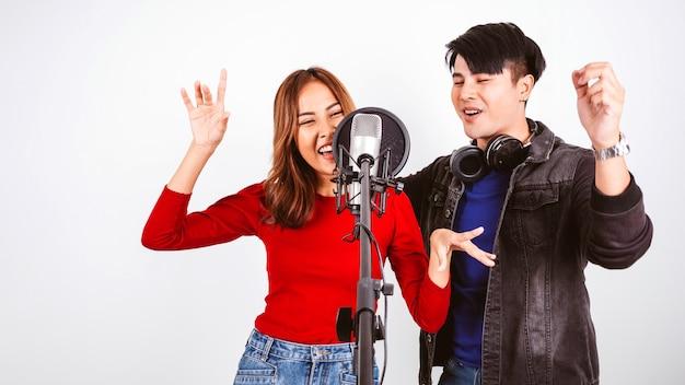 Cantores femininos e masculinos muito asiáticos gravando músicas usando um microfone de estúdio e escudo pop no microfone com paixão em fundo branco de estúdio de gravação de música. sessão de dueto.
