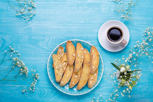 Cantuccini de biscoitos tradicionais da toscana italiana com amêndoas, uma xícara de café na luz