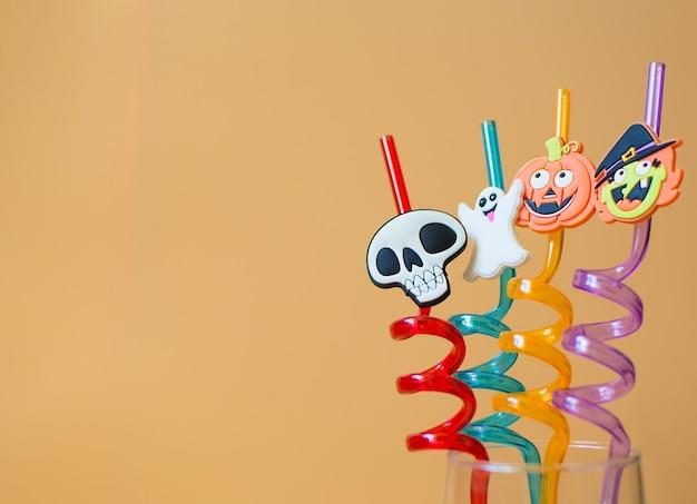 Canudinhos com decoração de halloween em vidro. decorações divertidas para bebidas de bebê. fantasma, bruxa, abóbora e caveira em palhas.