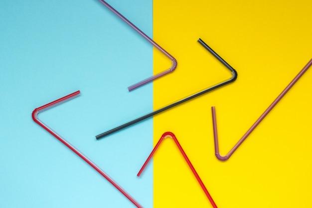 Canudo curvado multicolorido sobre um fundo azul e amarelo
