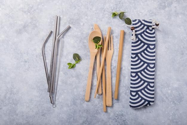 Canudo de metal reutilizável ecológico e talheres (colher, faca, garfo) na mesa de madeira. conceito de desperdício zero