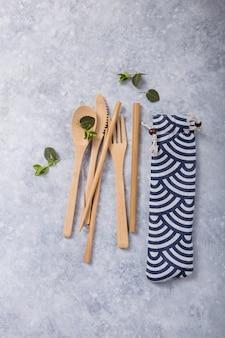 Canudo reutilizável ecológico e talheres (colher, faca, garfo) na mesa de concreto. conceito de desperdício zero