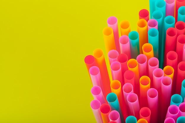 Canudos coloridos para bebidas refrigerantes em fundo colorido