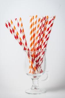 Canudos de coquetel listrados em um copo transparente