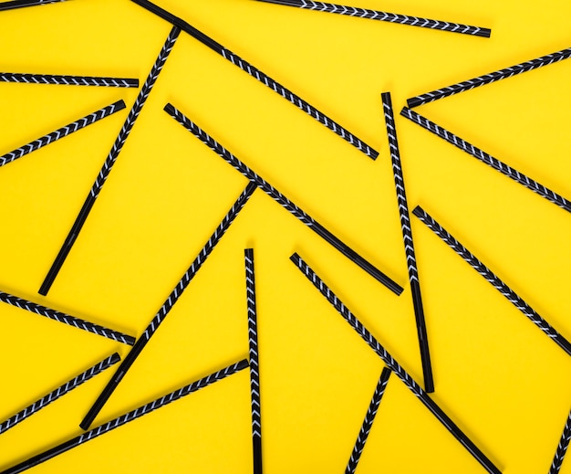 Canudos de coquetel preto espalhados em amarelo