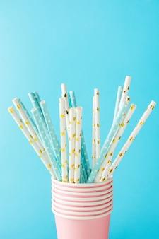 Canudos de papel branco e azul e copos-de-rosa