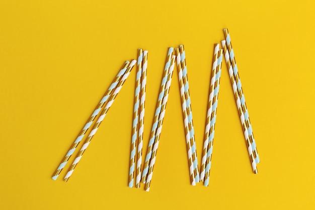 Canudos de papel brilhante com padrão listrado dourado sobre fundo amarelo, com espaço de cópia. conceito para festa ou aniversário. postura plana. vista do topo.