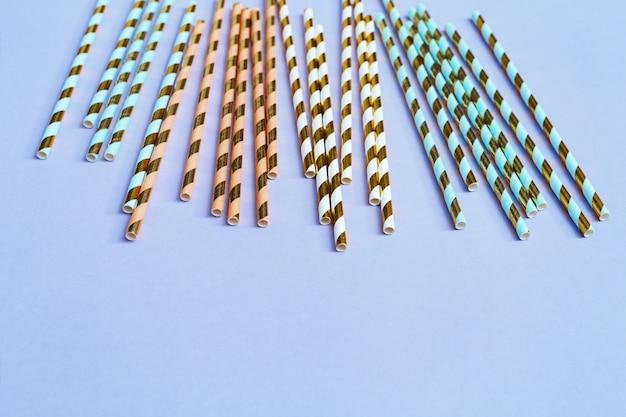 Canudos de papel brilhante com padrão listrado dourado sobre fundo azul, com espaço de cópia. conceito para festa ou aniversário. postura plana. vista do topo.