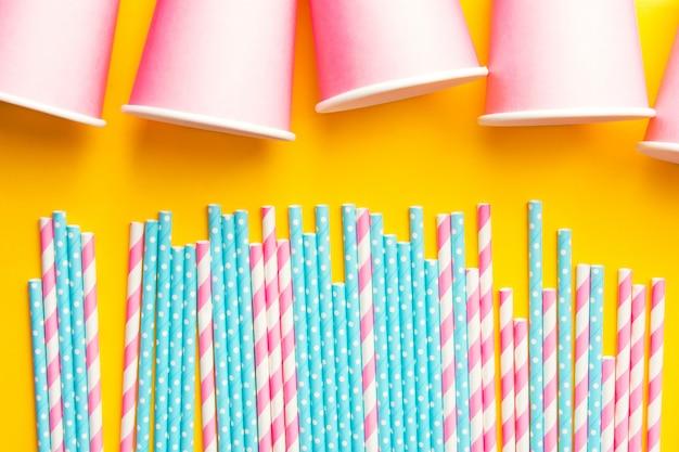 Canudos de papel rosa e azul e copos-de-rosa