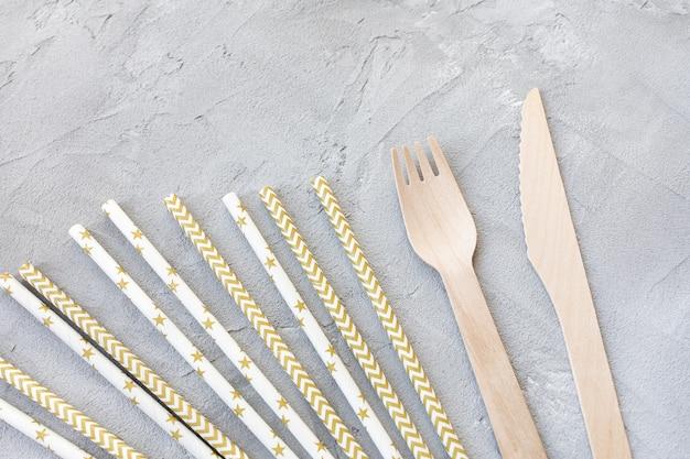 Canudos descartáveis de papel ecologicamente corretos e talheres de madeira na cor cinza, facas e garfos