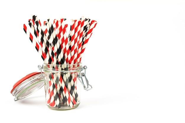 Canudos festivos de papel para bebidas em uma jarra de vidro sobre um fundo branco com um lugar para o texto