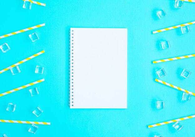 Canudos, gelo e caderno para receita de coquetel