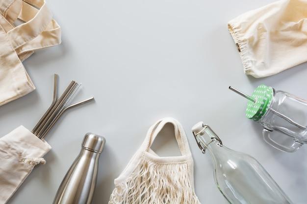 Canudos metálicos, saco de algodão, vidro e garrafa de metal em cinza.