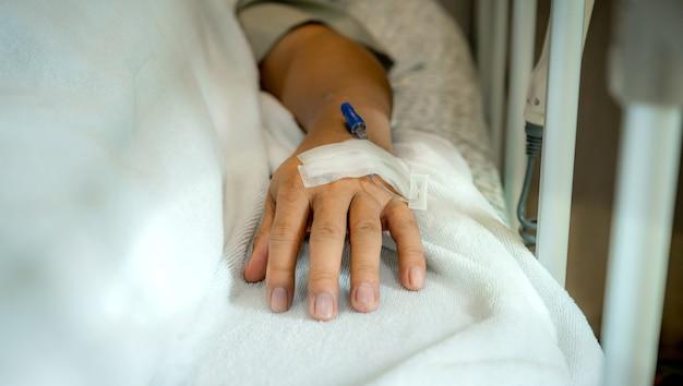 Cânula na mão do paciente do sexo masculino na cama na enfermaria