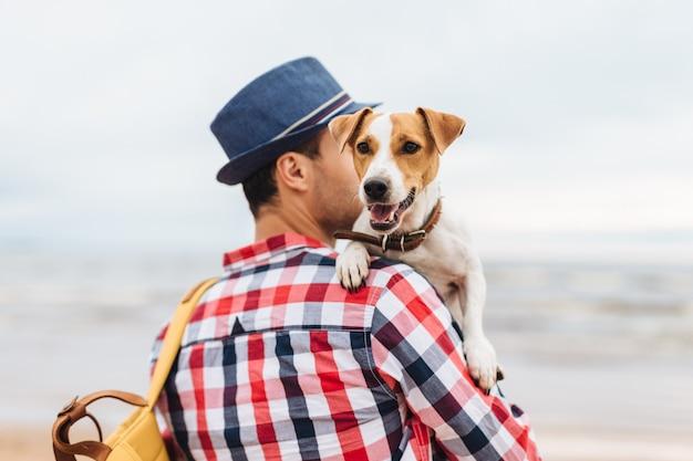 Cão bonito pequeno nas mãos do `s do proprietário. jovem macho carrega seu animal de estimação e bolsa, fica à beira-mar