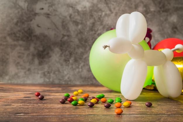 Cão branco feito com balão e doces coloridos na mesa de madeira