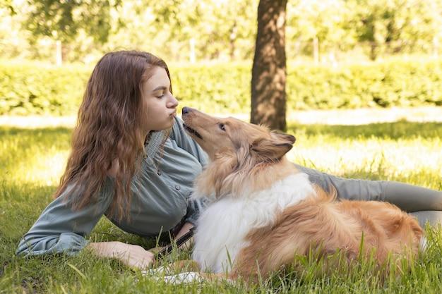 Cão collie lambe o rosto de menina, amor por cães de estimação